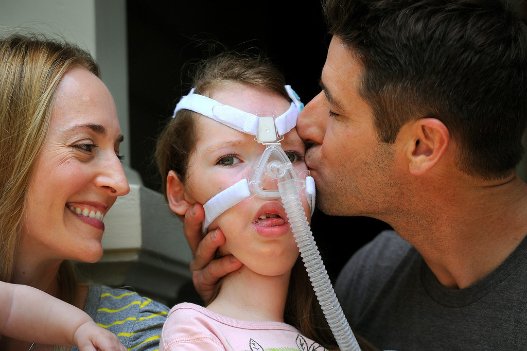 . Bill Strong kisses his daughter Gwendolyn as wife Victoria looks on. Gwendolyn was born with spinal muscular atrophy. (Photo by Michael Owen Baker/Los Angeles Daily News)