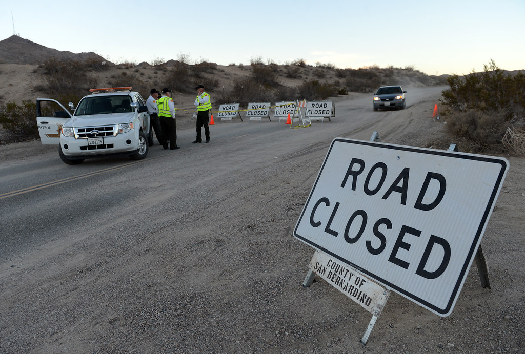 . San Bernardino County Sheriffs investigators enter and exit the area where the remains of four victims were found buried in two shallow graves in the desert just north of Victorville Wednesday, November 13, 2013. (Photo by Jennifer Cappuccio Maher/Inland Valley Daily Bulletin)