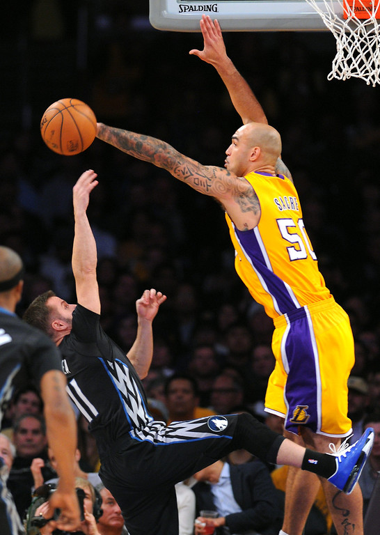 . The Lakers\' Robert Sacre blocks a shot by the Timberwolves\' J.J. Barea in the first half, Friday, December 20, 2013, at Staples Center. (Photo by Michael Owen Baker/L.A. Daily News)