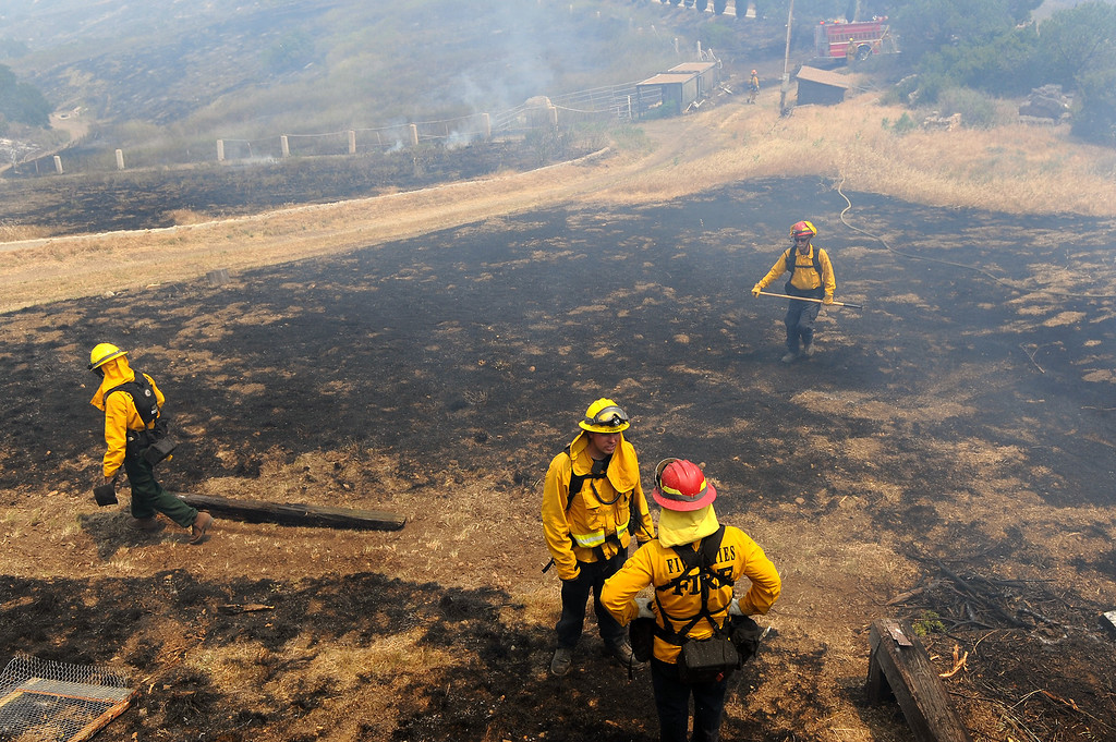 . Firefighters mop up a charred hillside by a house on Deer Creek Road in Ventura County, Friday, May 3, 2013. (Michael Owen Baker/Los Angeles Daily News)