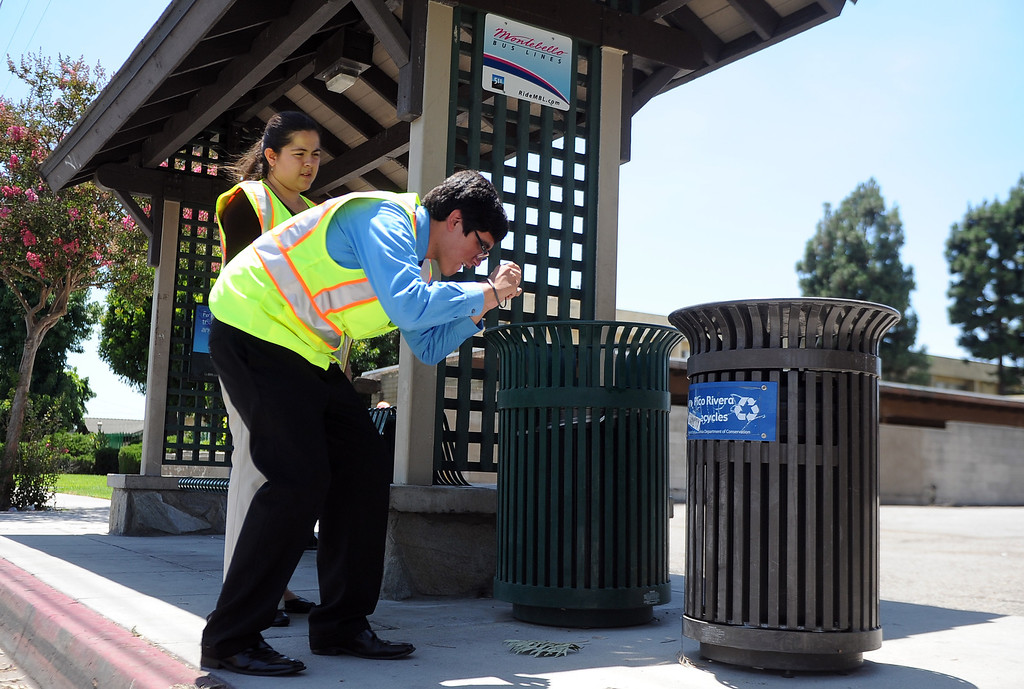 . Robert Sanchez a La Serna graduate takes a photograph of a trash can as Interns Monserrat Marquez a former El Rancho graduate looks on as they inspect a bus stop at the corner of Passons Blvd and Jackson Street as part of the Pico Rivera college prep program on Tuesday, July 16, 2013 in Pico Rivera, Calif.   (Keith Birmingham/Pasadena Star-News)
