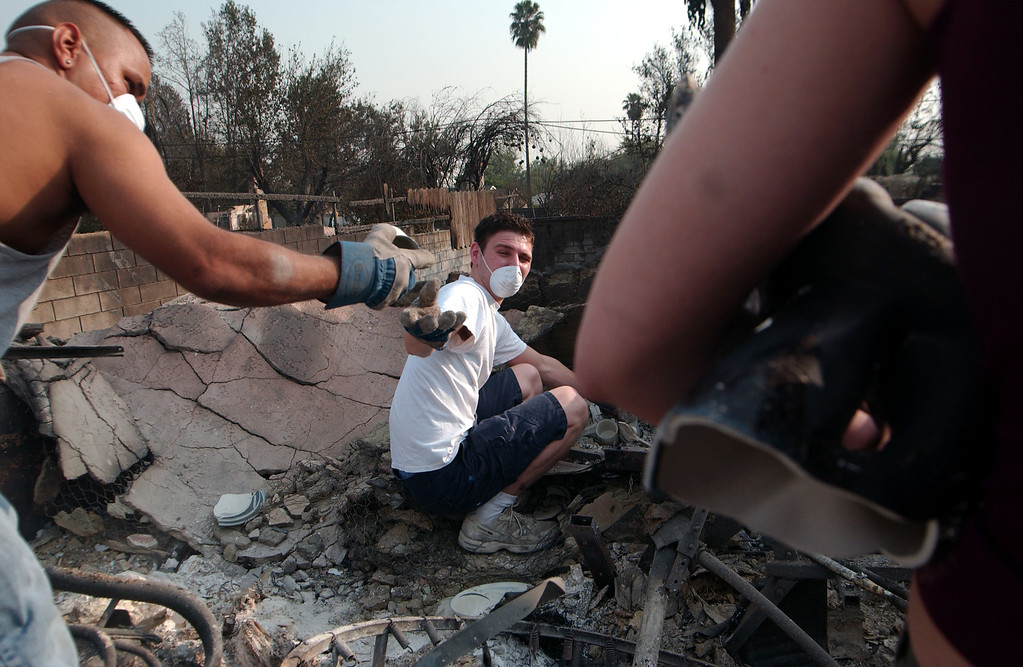 . Ten years ago this month the arson caused Old Fire, fanned by Santa Ana winds burned thousands of acres, destroyed hundreds of homes and caused six deaths. The fire burned homes in San Bernardino, Highland, Cedar Glen, Crestline, Running Springs and Lake Arrowhead and forced the evacuation of thousand of residents.  Ray Roybal, 21, left, takes a tea cup from Josh Levesque, 21,  he found in the rubble of his friend Kristian Crocfer\'s, right, San Bernardino home which burned during the Old Fire. (Staff file photo/The Sun)