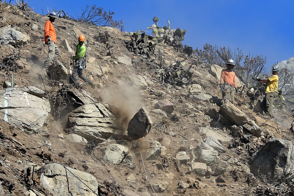 . Workers dislodge rocks from a hillside above PCH south of Pt. Mugu, Monday, November 25, 2013, during a scaling project to bring down potentially dangerous rocks on a hillside that was burnt during the Springs Fire last May. A steel mesh netting will be placed over the hillside in a couple weeks. (Photo by Michael Owen Baker/L.A. Daily News)