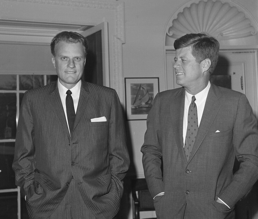 . Evangelist Billy Graham, left, talks with President John F. Kennedy during a call at the President\'s White House office, Dec. 12, 1961.  (AP Photo)