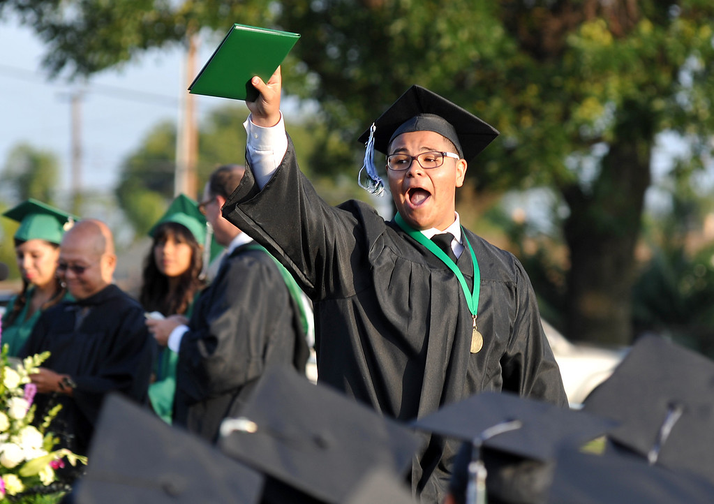 . Jerad Catola shows his diploma as he yells back to family during the 53rd Commencement at Pioneer High School in Whittier on Wednesday June 12, 2013. (SGVN/Staff Photo by Keith Durflinger)