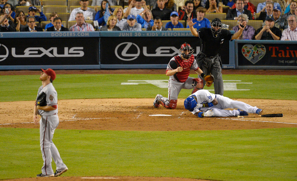 . Los Angeles Dodgers\' Yasiel Puig, below, is seen to by Arizona Diamondbacks catcher Miguel Montero, second from left, after being hit by a pitch as home plate umpire Clint Fagan signals and starting pitcher Ian Kennedy looks on during the sixth inning of their baseball game, Tuesday, June 11, 2013, in Los Angeles.  (AP Photo/Mark J. Terrill)