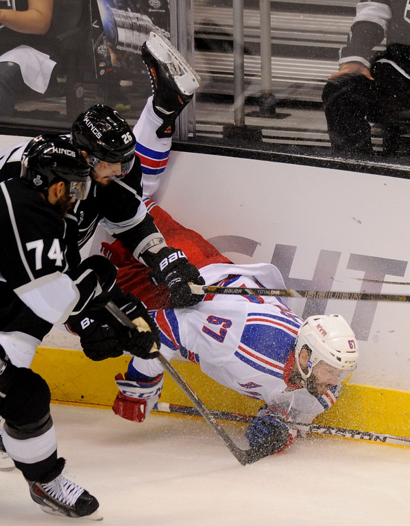 . The Rangers\' Benoit Pouliot does a faceplant with the help of the Kings\' Slava Voynov in the third period of game two of the Stanley Cup Final, Saturday, June 7, 2014, at Staples Center. (Photo by Michael Owen Baker/Los Angeles Daily News)