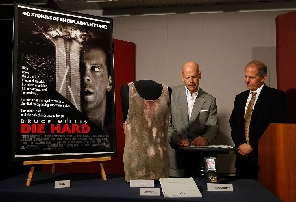 ". WASHINGTON - JUNE 27:  Actor Bruce Willis (L) signs an agreement with Director of the National Museum of American History Brent Glass (R) where Willis agreed to donate objects from the ""Die Hard\"" series of films to the Smithsonian\'s National Museum of American History June 27, 2007 in Washington, DC. A selection of \""Die Hard\"" items will go on display in the new acquisitions case in the museum\'s \""Treasures of American History\"" exhibition at the Smithsonian.  (Photo by Win McNamee/Getty Images)"