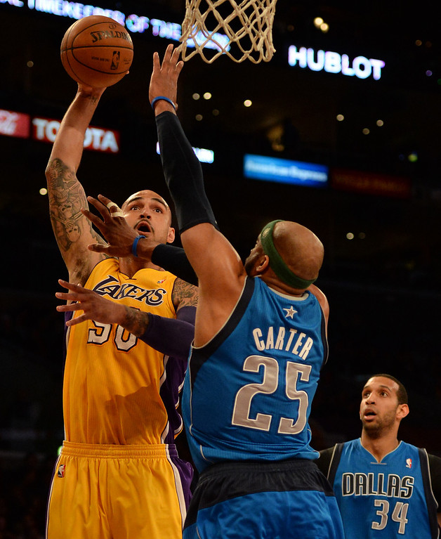 . Los Angeles Lakers center Robert Sacre (50) shoots over Dallas Mavericks guard Vince Carter (25) as Brandan Wright (34) looks on in the first quarter during an NBA basketball game in Los Angeles, Calif., on Friday, April 4, 2014.  (Keith Birmingham Pasadena Star-News)