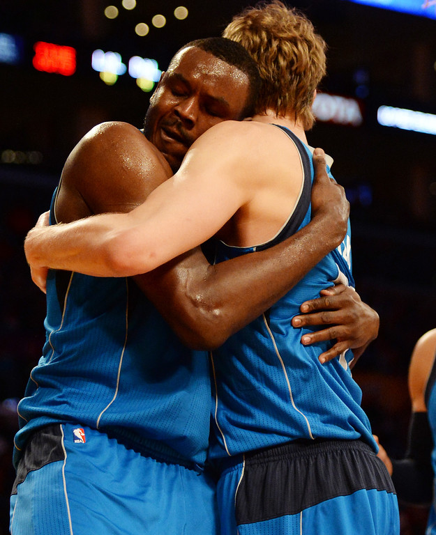 . Dallas Mavericks center Samuel Dalembert, left, hugs teammate Dirk Nowitzki after scoring in the second half during an NBA basketball game against the Los Angeles Lakers in Los Angeles, Calif., on Friday, April 4, 2014. Dallas Mavericks won 107-95.  (Keith Birmingham Pasadena Star-News)