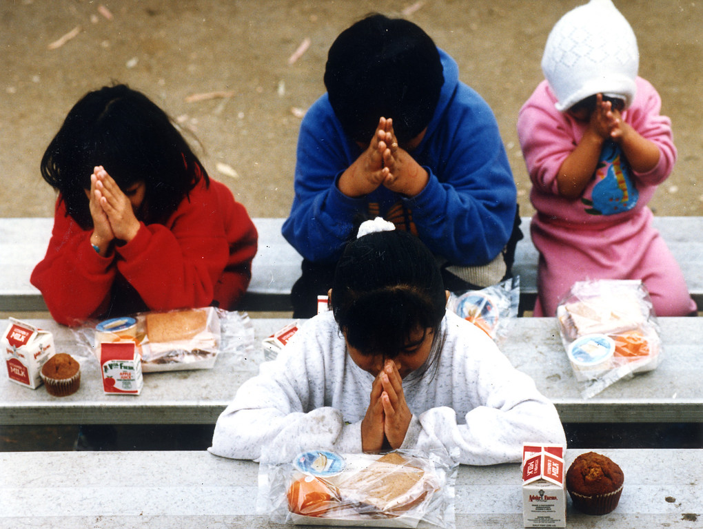 . Belen Navarro, 9, front, leads her sisters and cousins in prayer before eating their lunches at a tent city.   Michael Owen Baker/Los Angeles Daily News
