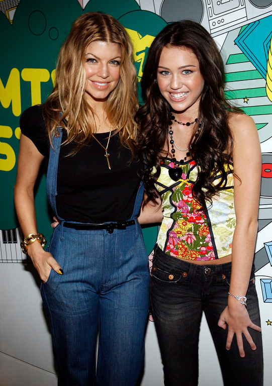 """. Singer Fergie, left, and actress/singer Miley Cyrus pose backstage during MTV\'s \""""Total Request Live\"""" at the MTV Times Square Studios Monday, June 18, 2007 in New York.  Fergie is currently on her first solo tour since leaving the Black Eyed Peas.  Cyrus\' latest album \""""Hannah Montana 2: Meet Miley Cyrus\"""" hits stores June 26, 2007.  (AP Photo/Jason DeCrow)"""