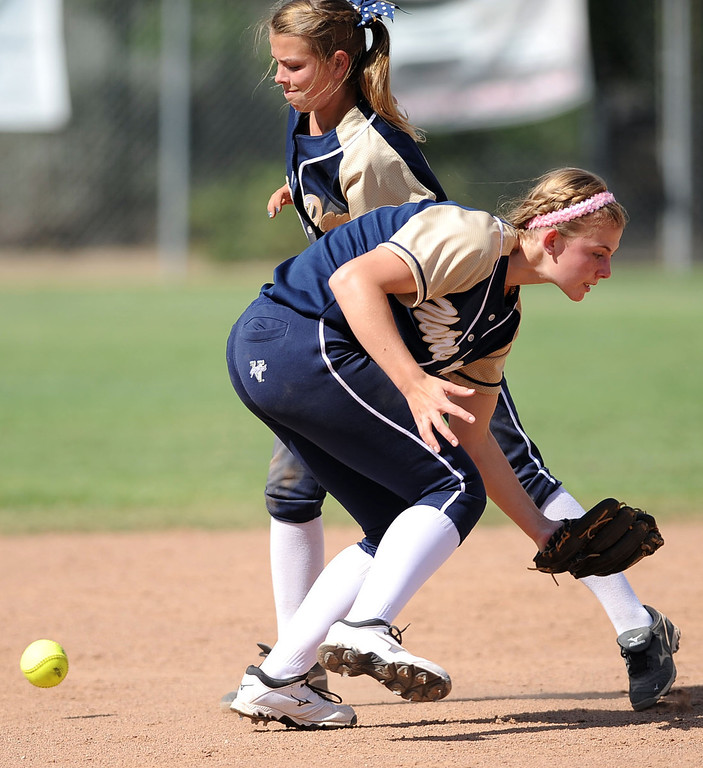 . Notre Dame shortstop Emily Waters and Annika Pearson can\'t make a play on an Alemany groundball during their Mission League softball showdown in Encino, CA April 8, 2014.  Alemany won the game, 5-4.(Andy Holzman/Los Angeles Daily News)