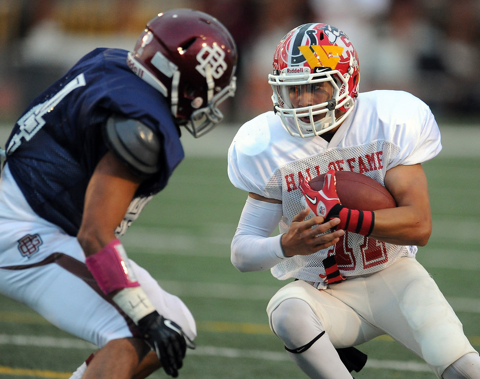 . East\'s Kevin Amezquita (11) (Gladstone) runs for yardage against West\'s Christopher Mendoza (44) (Bell Gardens) in the first half of the annual East vs. West San Gabriel Valley Hall of Fame all-star football game at West Covina High School on Friday, May 17, 2013 in West Covina, Calif. 