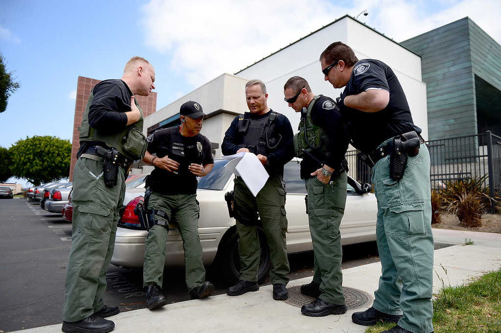 . Los Angeles County Special Enforcement Probation officers, from left, Aldin Tatley, Angel Gonzalez, Jim Shrout John Perico and Jon Reinke go over a sex offender\'s case before conducting a compliance check Thursday, April 25, 2013 in Los Angeles. The county has 30 armed probation officers and is seeking more armed officers to deal with realignment, the release of low-level inmates from state to county supervision. (SGVN/Staff Photo by Sarah Reingewirtz)