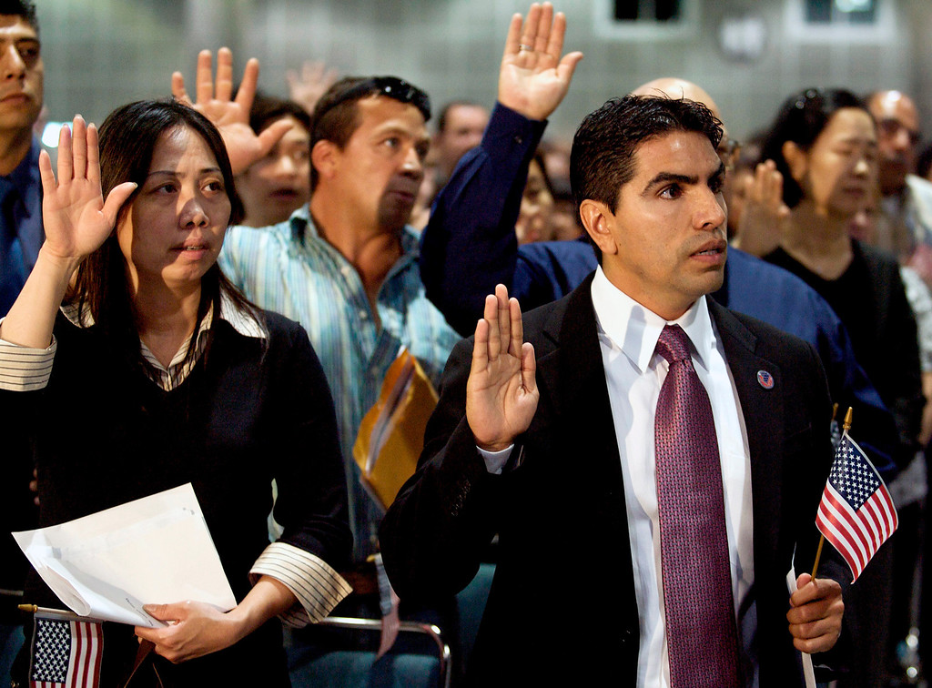 ". In this May 22, 2008, Eddie ""Piolin\"" Sotelo, right, host of Univision Radio\'s nationally syndicated morning show, takes the oath during naturalization ceremonies at the Los Angeles Convention Center. \""Piolin\"" is the voice of the most popular Spanish-language radio show in the U.S.  (AP Photo/Damian Dovarganes, file)"