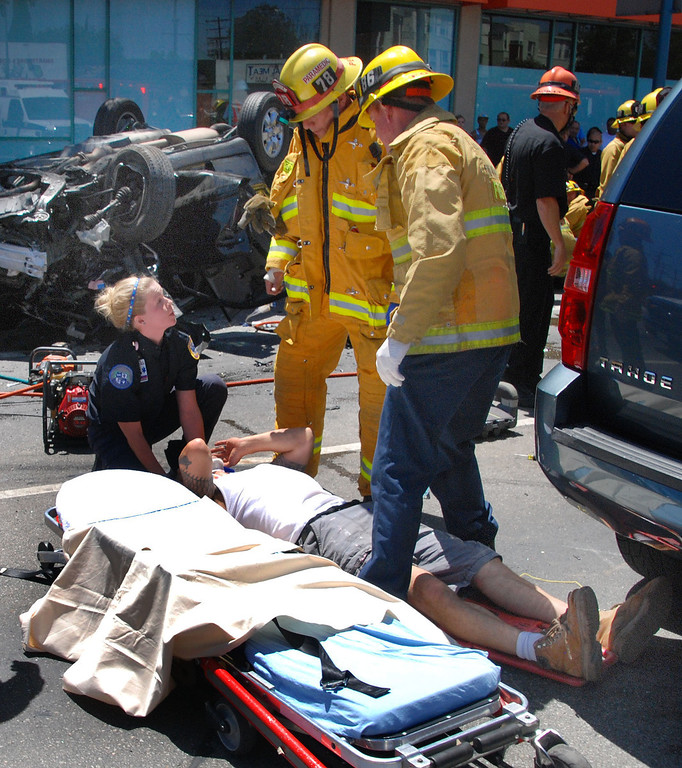 . North Hollywood, Ca. LAFD firefighters help the attendant of a private ambiulance service that was first on the scene of a horrible traffic accident that left one dead and 4 others injured. The accident happed at lankershim Bl and Vineland Av in North Hillywood around 2pm this afternoon. The accident left an overturned SUV with the front end totally gone.