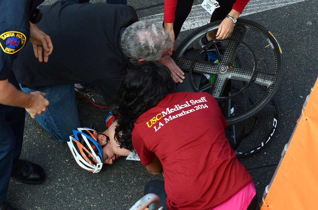 . 2014 ASICS LA Marathon women\'s wheelchair winner Susannah Scaroni  is treated after she crashed  crossing the finish line in Santa Monica Calif, with a time of 1: 54: 54.   Sunday, March 9,  2014.   (Photo by Stephen Carr / Daily Breeze)