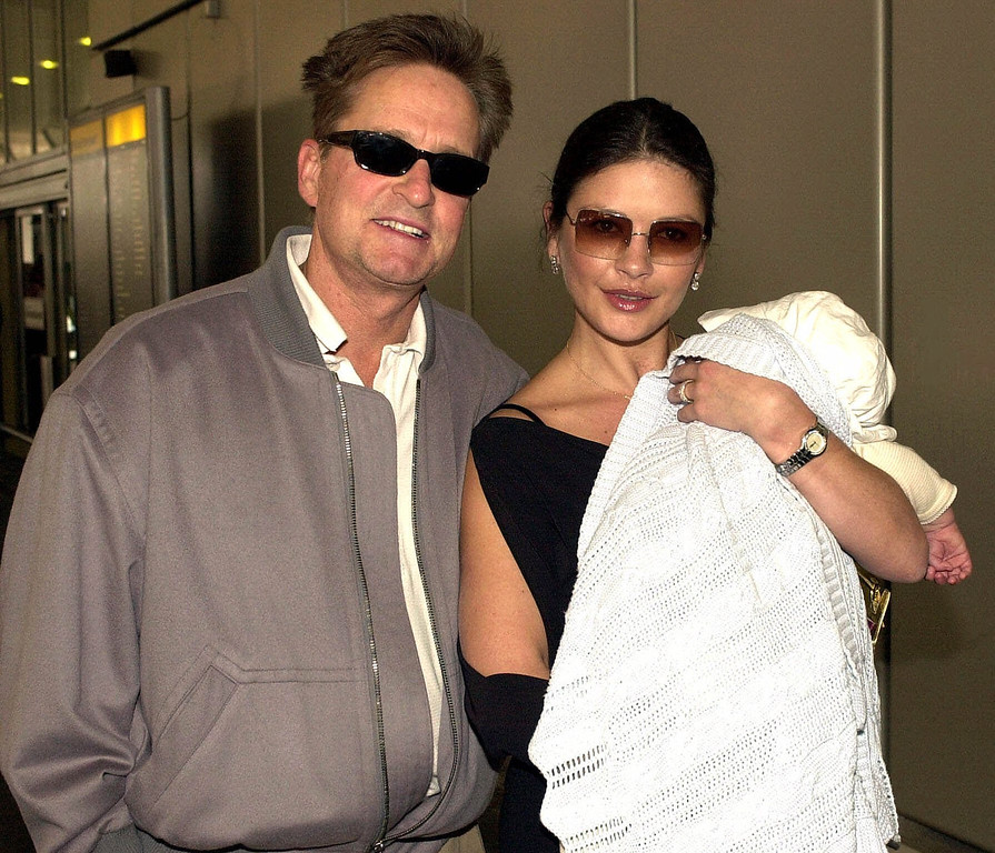 . Actors Michael Douglas and Catherine Zeta-Jones arrive at London\'s Heathrow Airport from Los Angeles with their son Dylan Wednesday, August 1, 2001. (AP Photo)