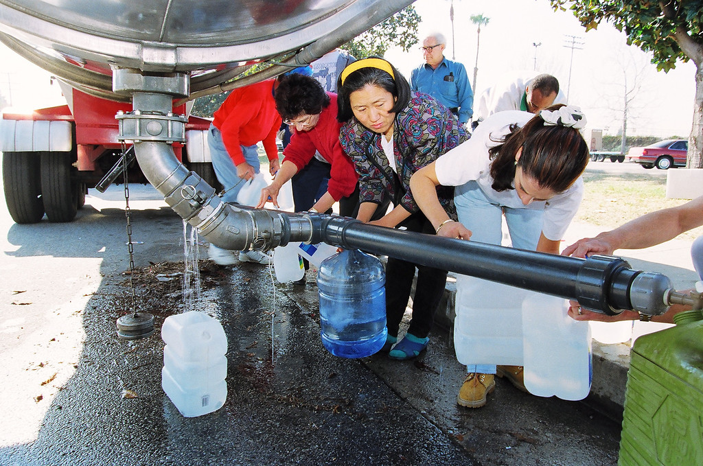 . Their water service cut off, Granada Hills residents fill containers from a water company truck at Granada Hills High School.   John McCoy/Los Angeles Daily News