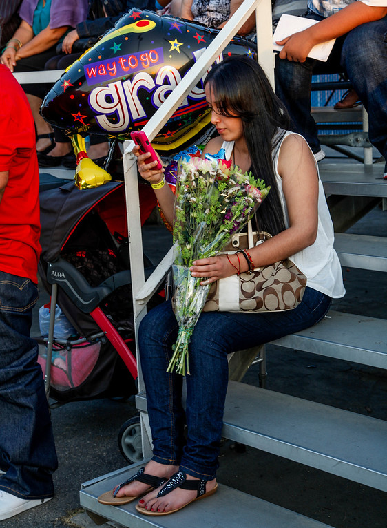 . Rebeca Martinez, holding flowers and a phone, waits to find the location her graduating sister will meet her, at John H Francis Polytechnic High School, Sun Valley, Calif., June 7, 2013. Photo: Lynn Levitt.