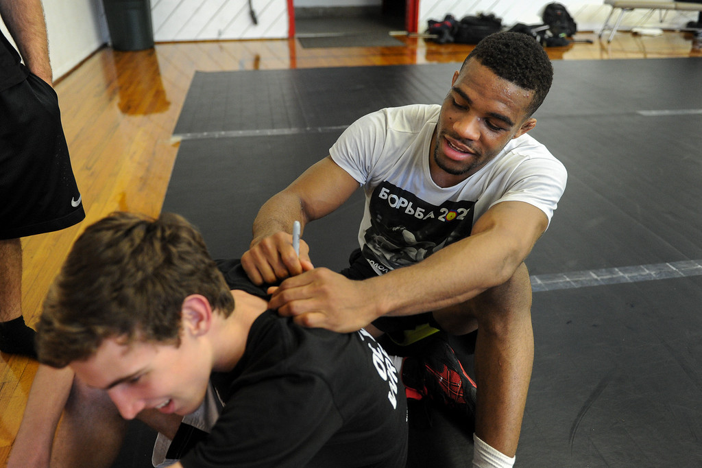 . The U.S. national wrestling team member Jordan Burroughs signs a shirt for Patrick Halkett following practice at Harvard-Westlake High School, Friday, May 17, 2013.