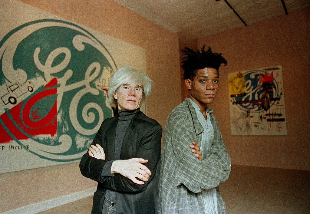 ". Pop artists Andy Warhol, left, and Jean-Michel Basquiat pose in front of their collaborative paintings on display at the Tony Shafrazi Gallery in Manhattan\'s SoHo section, New York, September 24, 1985.  They  collaborated on 16 untitled canvases.  Warhol painted the company logos and Basquiat, who has roots in the graffiti movement, added dashes of color and commentary.  Warhol, working in oils for the first time since 1962, said of the collaboration: ""I just did some, and he did some.  We didn\'t think too much about it.  It was fun doing.\""  The canvases were offered at between $50,000 and $80,000 a piece.  (AP Photo/Richard Drew)"
