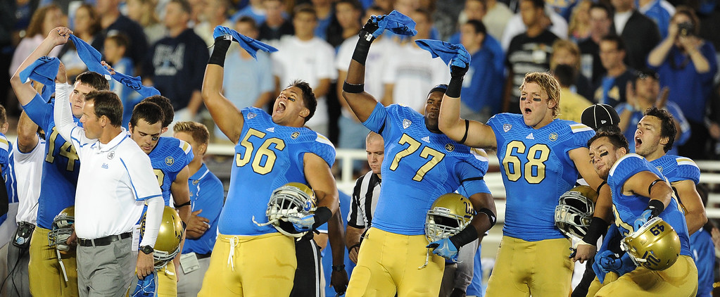 . UCLA athletes wave towels that were handed out in honor of Nick Pasquale, the UCLA receiver who was struck and killed by a car earlier this month prior to their college football game against New Mexico State in the Rose Bowl in Pasadena, Calif., on Saturday, Sept. 21, 2013.   (Keith Birmingham Pasadena Star-News)
