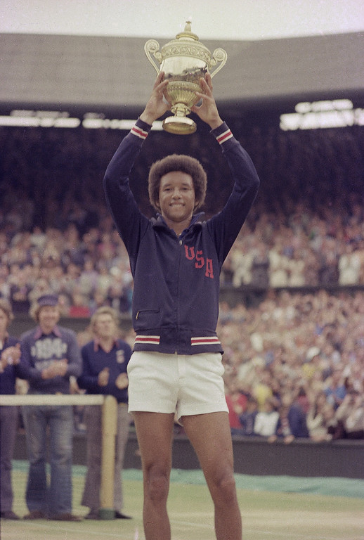. Arthur Ashe holds his Wimbledon trophy up after defeating fellow American Jimmy Connors in the final match of the men\'s singles championship at the All England Lawn Tennis Championship in Wimbledon, England, July 5, 1975.  (AP Photo)