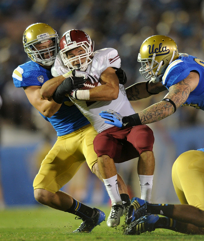 . New Mexico State RB Brandon Betancourt is tackled by UCLA\'s Jordan Zumwalt, left, and Cassius Marsh in the first half, Saturday, September 21, 2013, at the Rose Bowl. (Photo by Michael Owen Baker/L.A. Daily News)