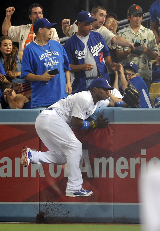 . Dodgers right fielder Yasiel Puig crashes into the outfield wall while casing a home run ball by the Giants Hunter Pence in the second inning, Thursday, September 12, 2013, at Dodger Stadium. (Photo by Michael Owen Baker/L.A. Daily News)