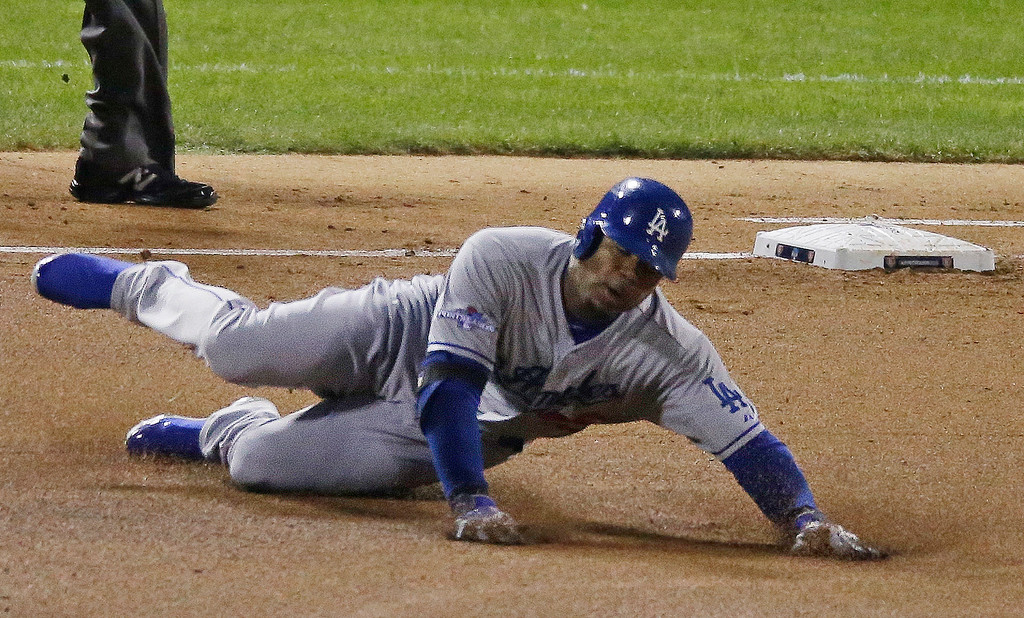 . Los Angeles Dodgers\' Carl Crawford trips as he rounds first after hitting a double during the third inning of Game 1 of the National League baseball championship series against the St. Louis Cardinals, Friday, Oct. 11, 2013, in St. Louis. (AP Photo/Chris Carlson)