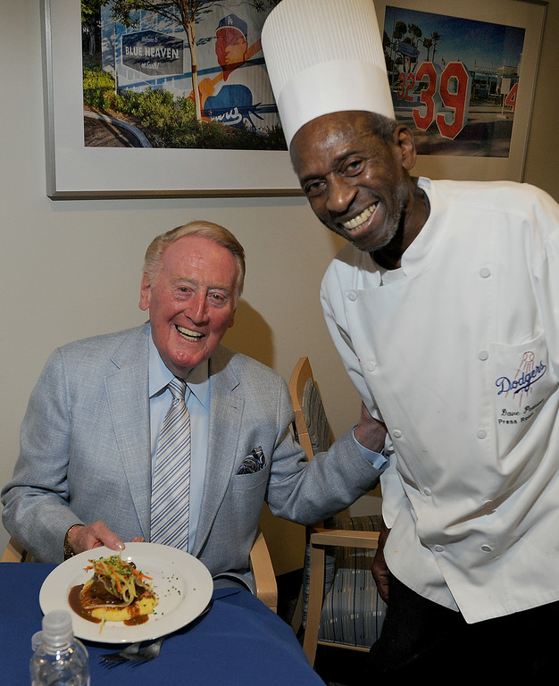 . Vin Scully with a meal served up by Dave Pearson who has been cooking up meals in the Dodger Press box for many years.  Los Angeles, CA. 8/19/2014(Photo by John McCoy Daily News)