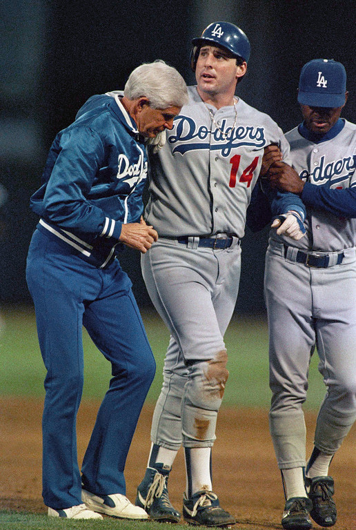. Injured Los Angeles Dodgers catcher Mike Scioscia (14) is helped from the field by trainer Bill Buhler, left, and first base coach Manny Mota in the fourth inning of the fourth game of the World Series against the Oakland As at Oakland Coliseum, Wednesday, Oct. 19, 1988, Oakland, Calif. Scioscia was injured sliding into second on a failed hit and run play. (AP Photo/Rusty Kennedy)