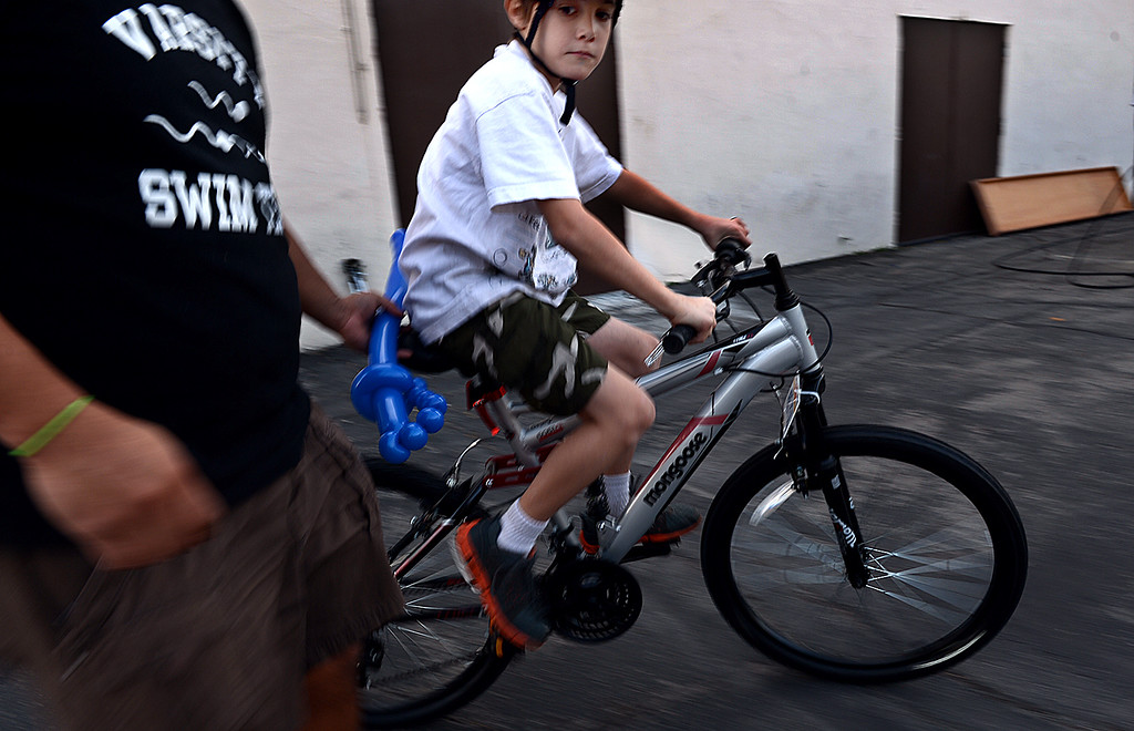 . Andrew Combs, 8, of San Bernardino takes his new bicycle for a spin with the help of his father Ruben Quiroz. Southern California Honda Dealers� Helpful Guys in Blue hosted a Santa�s Workshop Monday December 16, 2013 building bicycles for children of the Westside Kinship Support Program at St Paul\'s Methodist Church. There was also cookie decorating, face painting, and a visit from Pedals the Clown. The Westside Kinship Support Program is a support system for caregivers who step in to raise extended family members� children who have been separated from or who have lost their parents.