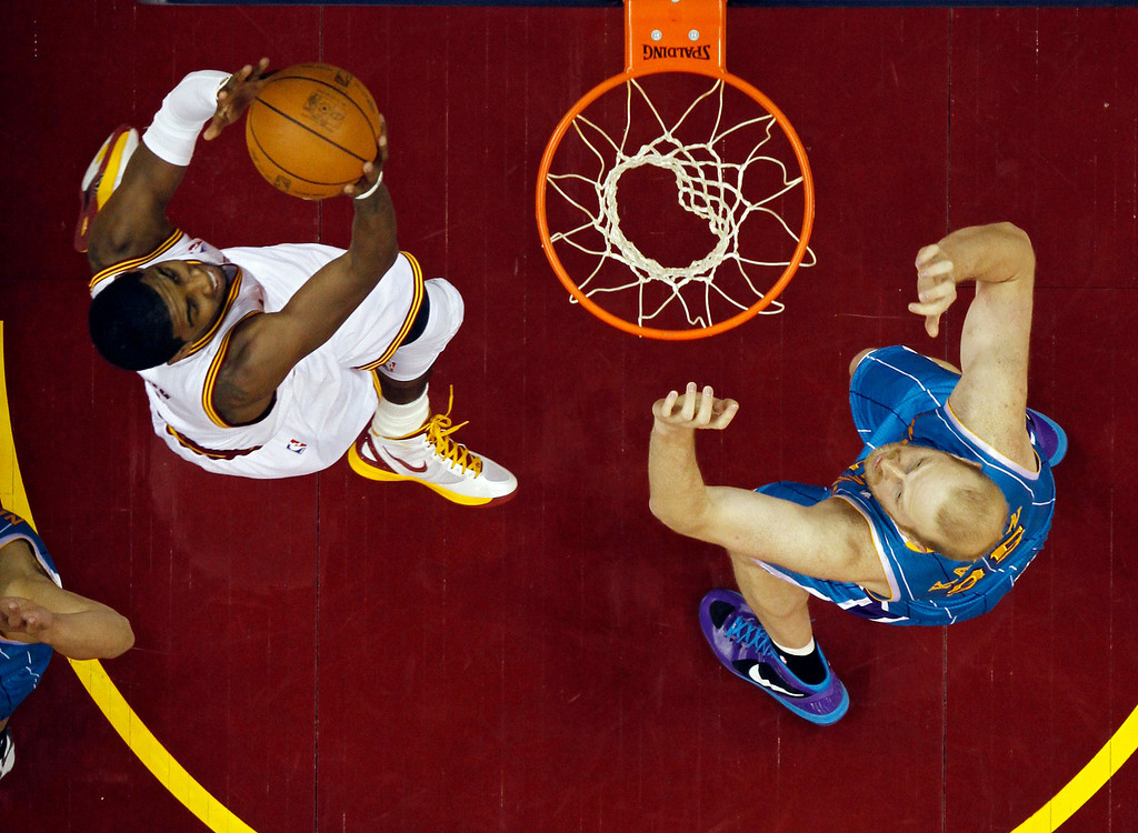 . Cleveland Cavaliers\' Kyrie Irving, left, goes in for a shot against New Orleans Hornets\' Chris Kaman in an NBA basketball game Wednesday, Feb. 22, 2012, in Cleveland. (AP Photo/Mark Duncan)