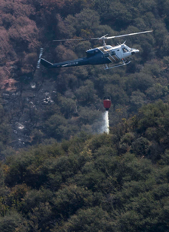 . A helicopter makes a drop on a hotspot near Point Mugu, Calif., Saturday, May 4, 2013. High winds and withering hot, dry air were replaced by the normal flow of damp air off the Pacific, significantly reducing fire activity. (AP Photo/Ringo H.W. Chiu)