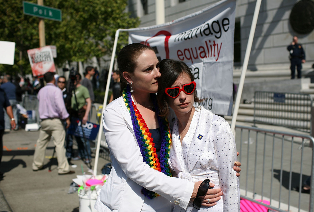 . SAN FRANCISCO - MAY 26:  Kerri McCoy (L) and her partner Erin Carder embrace following the California Supreme Court\'s ruling to uphold Proposition 8 May 26, 2009 in San Francisco, California. The California State Supreme Court voted 6-1 to uphold proposition 8 which makes it illegal for same-sex couples to marry in the state of California. More than 18,000 same-sex couples that wed before prop 8 was voted in will still be legally married.  (Photo by Justin Sullivan/Getty Images) *** Local Caption *** Kerri McCoy;Erin Carder