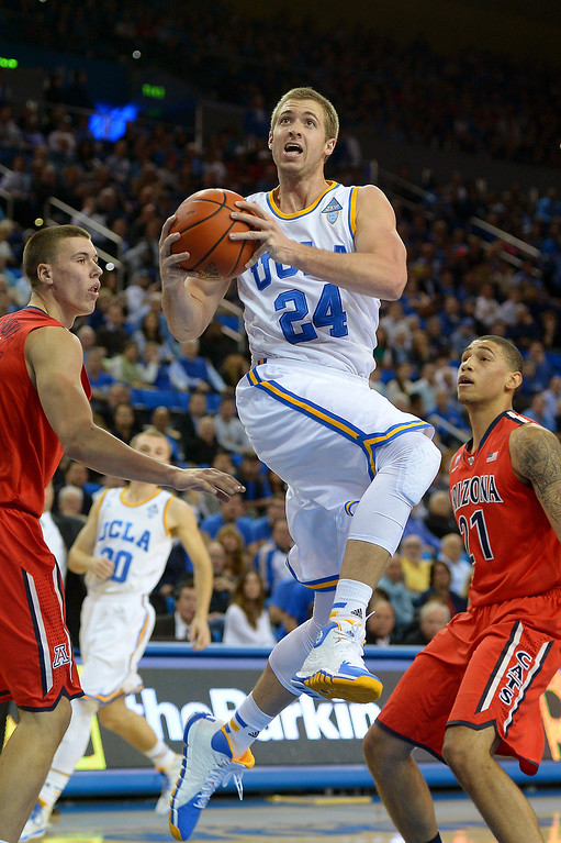 . UCLA\'s Travis Wear goes for a layup between Arizona\'s Kaleb Tarczewski, left, and Brandon Ashley in the first half, Thursday, January 9, 2014, at Pauley Pavilion. (Photo by Michael Owen Baker/L.A. Daily News)