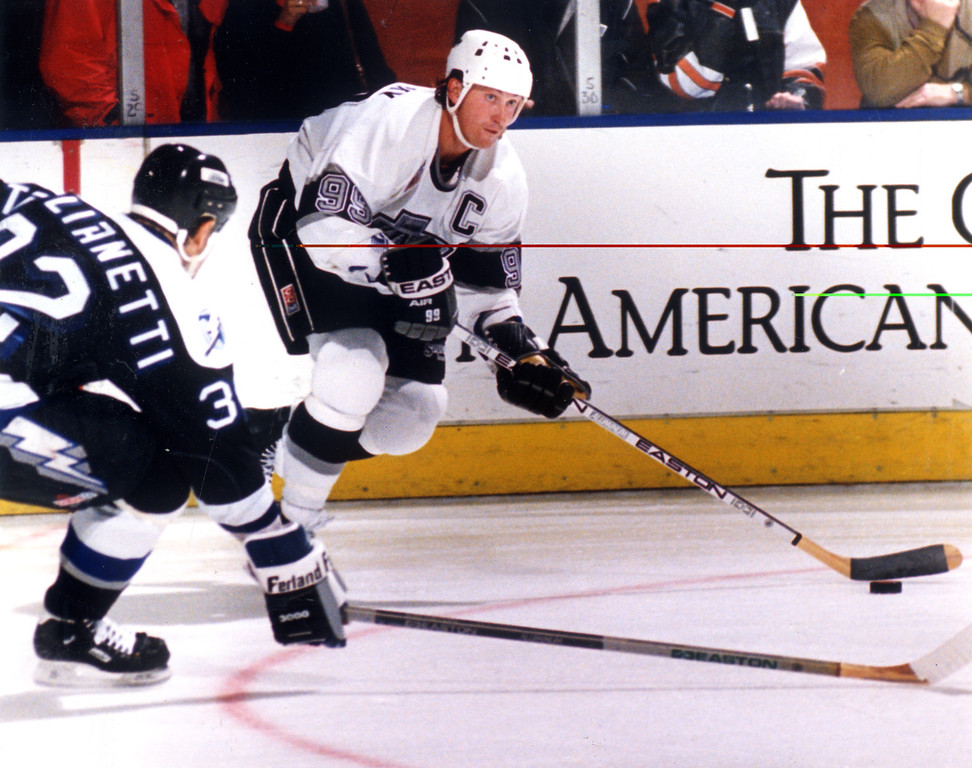 . Wayne Gretzky passes on 1/6/93 as Peter Taglianetti moves in.   L.A. Daily News file photo