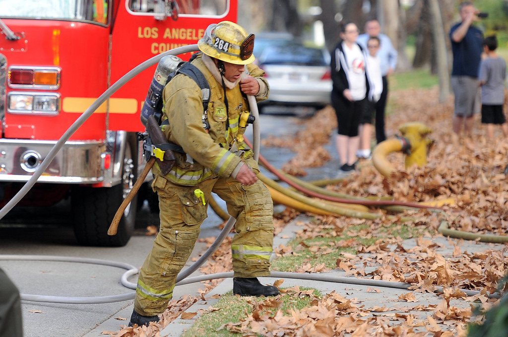 . A Los Angeles County Firefighter carries a water hose as they battle a fire that damaged a single family home. The fire started in the garage along the 1300 block of Via Verde. No injuries, but 5 cars were destroyed including two jaguars in San Dimas, Calif., on Saturday, Jan.4, 2014.   (Keith Birmingham Pasadena Star-News)