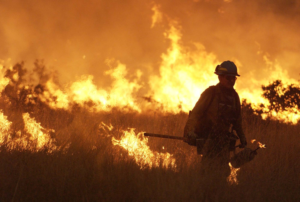 . Pat Peshlakai from the Navajo hot shots fire crew lights a back fire  top head off the front of the Cedar fire just outside Julian, Calif. Tuesday, October 28, 2003. (AP Photo/Tim Tadder)