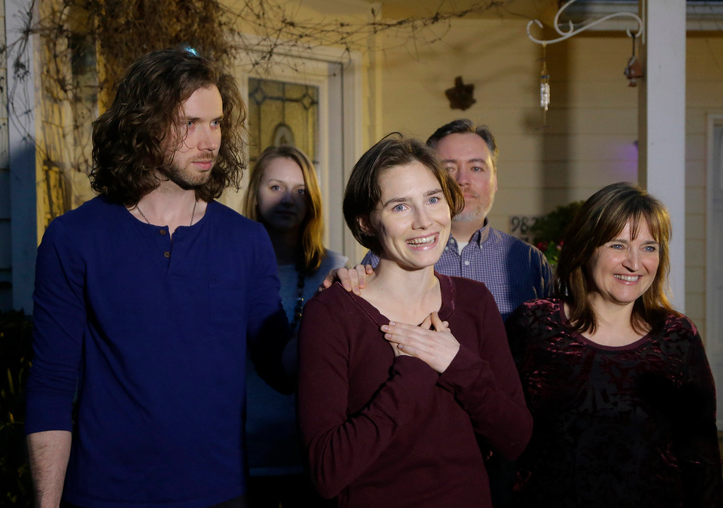 . Amanda Knox, center, stands with her mother, Edda Mellas, right, and her fiance, Colin Sutherland, left, as she talks to the media outside Mellas\' home, Friday, March 27, 2015, in Seattle. Italy\'s highest court overturned the murder conviction against Knox and her ex-boyfriend Friday over the 2007 slaying of Knox\'s roommate, bringing to a definitive end the high-profile case. (AP Photo/Ted S. Warren)