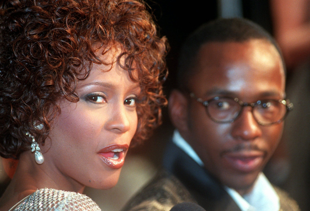 """. Whitney Houston looks over her shoulder as her husband Bobbi Brown looks to her at the premiere of \""""The Wonderful World of Disney\"""" movie \""""Cinderella,\"""" at Mann\'s Chinese Theater in the Hollywood section of Los Angeles, Monday, Oct. 13, 1997.  (AP Photo/Rene Macura)"""