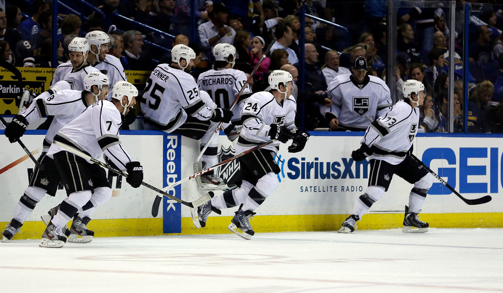 . Members of the Los Angeles Kings rush off the bench to congratulate teammate Slava Voynov, of Russia, on his game-winning goal during overtime in Game 5 of a first-round NHL hockey Stanley Cup playoff series against the St. Louis Blues Wednesday, May 8, 2013, in St. Louis. The Kings won 3-2. (AP Photo/Jeff Roberson)