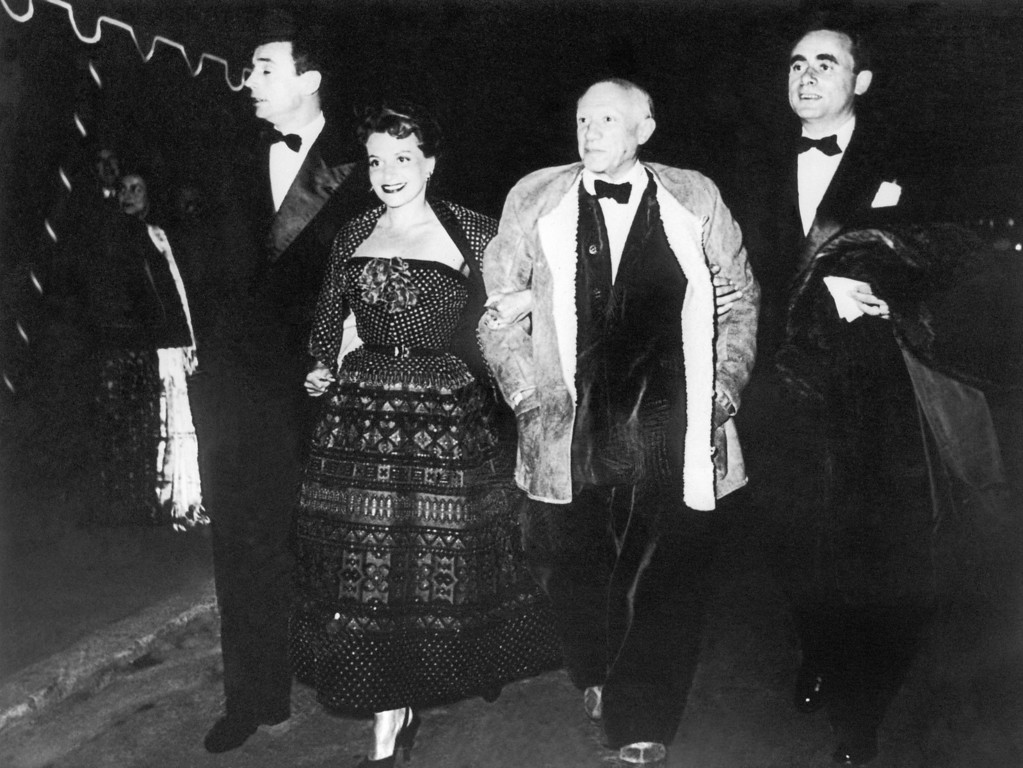 ". Wearing a fur-lined leather jacket over a velvet suit and with a bow tie, Spanish artist Pablo Picasso, strolls arms in arm with Vera Clouzot, wife of the director of the film ""Wages of Fear\"" at the Fifth International Film Festival in Cannes, France on April 15, 1953. Because of his attire, the organizers of the festival were at first reluctant to admit him but on Picasso\'s own insistence they let him in. At left French actor Yves Montand and French film director Georges-Henri Clouzot at right. (AP Photo)"