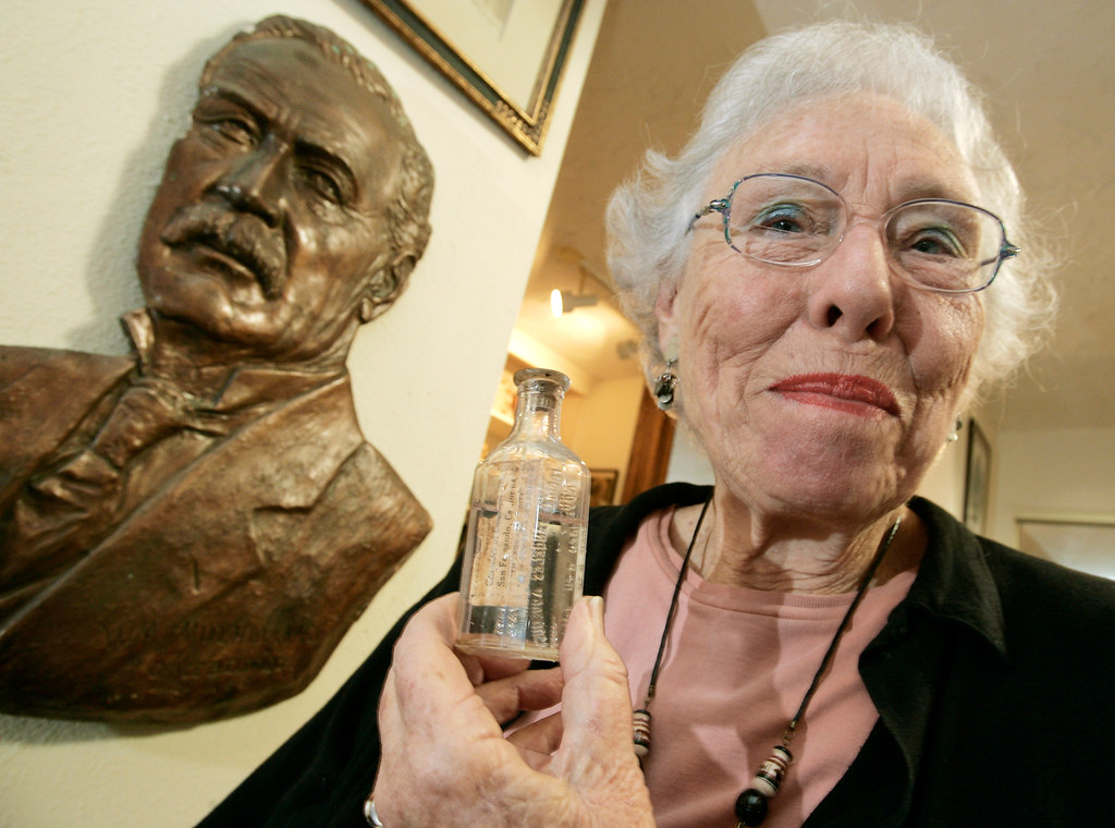 . Catherine Mulholland, granddaughter of William Mulholland, mastermind of the Los Angeles Aqueduct, poses next to a bust of her grandfather and holds a souvenir glass bottle, filled with water that rushed through the aqueduct when it was opened by her grandfather in 1913, at her home in the Chatsworth area of Los Angeles, Friday, Dec. 1, 2006. Over the years, water diverted from the Owens Valley east of the Sierra Nevada has fed the growth of Los Angeles from a desert pueblo to one of the world\'s biggest cities. (AP Photo/Reed Saxon)