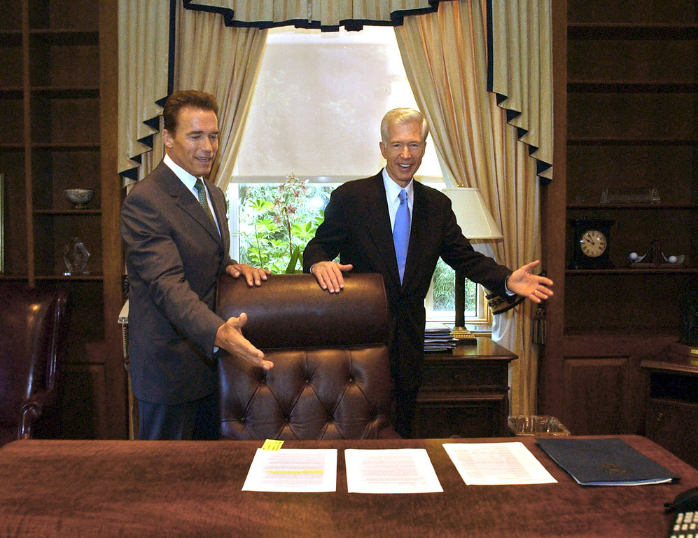. FILE - In this Oct. 23, 2003 file photo, Gov.-elect Arnold Schwarzenegger, left, and Gov. Gray Davis joke with each other as Davis shows Schwarzenegger the governor\'s private office at the Capitol in Sacramento, Calif. The two met for the first time since the election to go discuss the transition. Schwarzenegger will be leaving office in January 2011 with a mixed record, winning praise for his precedent-setting environmental activism and criticism for his failure to tame the fiscal mess as promised when voters  elected Schwarzenegger to replace Gov. Gray Davis in the historic 2003 recall election. (AP Photo/Rich Pedroncelli, File)