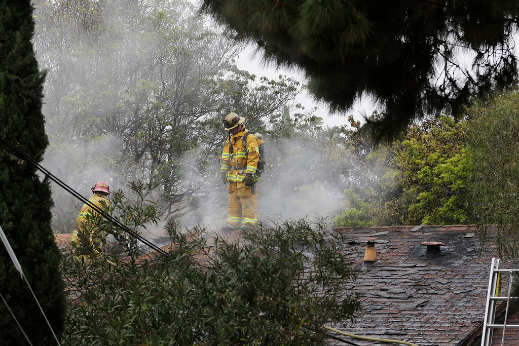 . Firefighters work at a burning home about a mile northeast of Santa Monica College in Santa Monica, Calif. Friday, June 7, 2013. Two people were found dead in the burned home where someone sprayed a street corner with gunfire, wounding at least three people, authorities said. (AP Photo/Reed Saxon)