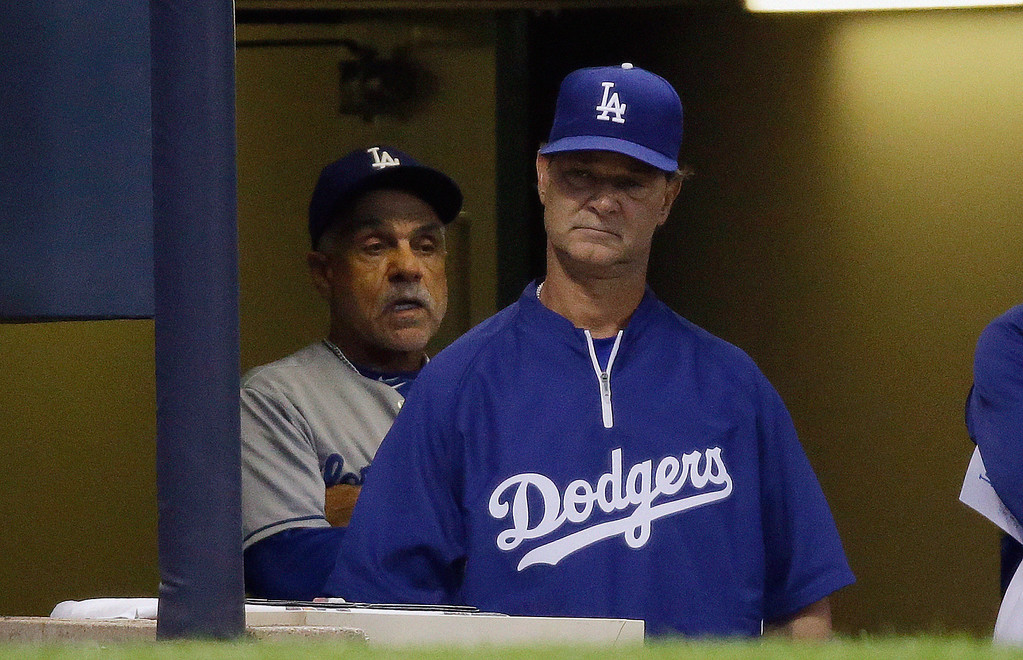 . Los Angeles Dodgers manager Don Mattingly watches from the dugout with first base coach Davey Lopes, left, during the third inning of a baseball game against the Milwaukee Brewers Wednesday, May 22, 2013, in Milwaukee. (AP Photo/Morry Gash)